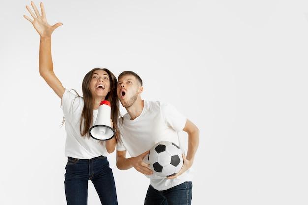 Portret van mooie jonge paarvoetbal of voetbalfans op witte studiomuur