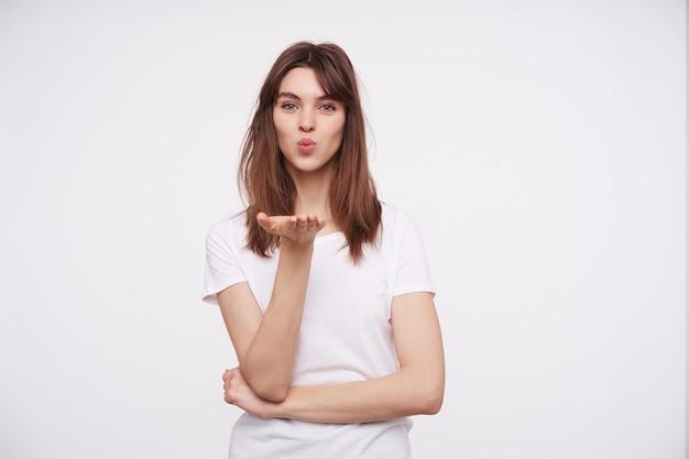 Portret van mooie jonge positieve donkerharige dame met casual kapsel dat haar lippen vouwt en luchtkus verzendt, de handpalm omhoog houdt terwijl ze over een witte muur poseren