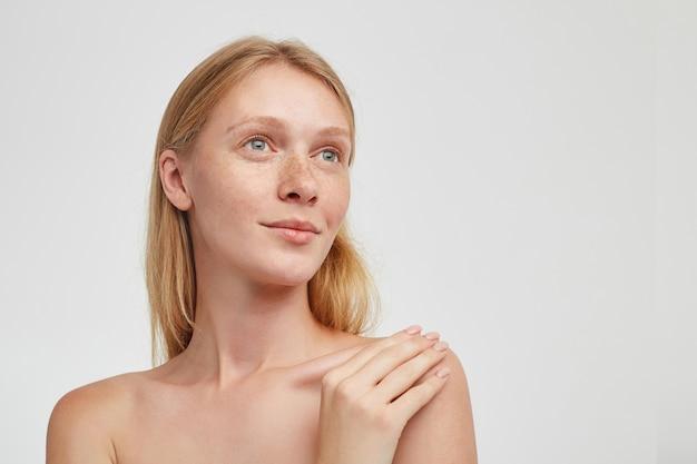 Portret van mooie jonge roodharige dame met casual kapsel hand op haar schouder houden en dromerig naar boven kijkend met lichte glimlach, staande over witte muur