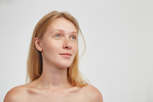 Portret van mooie jonge roodharige langharige vrouw met casual kapsel, rustig opzij kijken en haar lippen gevouwen houden, poseren over witte muur
