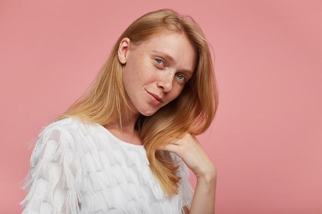 Portret van mooie jonge roodharige vrouw met casual kapsel, gekleed in een witte feestelijke blouse terwijl ze over roze achtergrond staat, haar lippen gevouwen houden terwijl ze zachtjes naar de camera kijkt