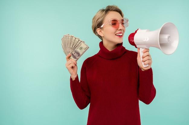 Portret van mooie jonge schreeuwende vrouw met geld en megafoon, op blauwe achtergrond - afbeelding