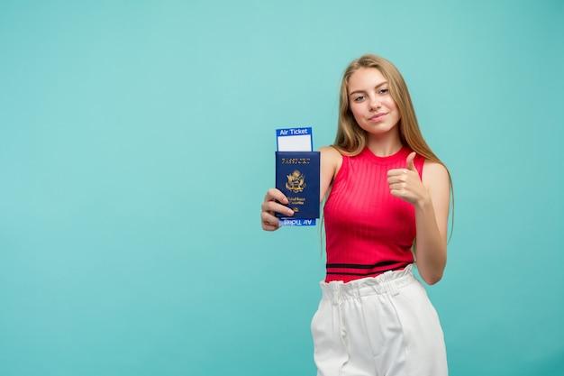 Portret van mooie jonge student vrouw met paspoort met kaartjes geïsoleerd op blauwe achtergrond