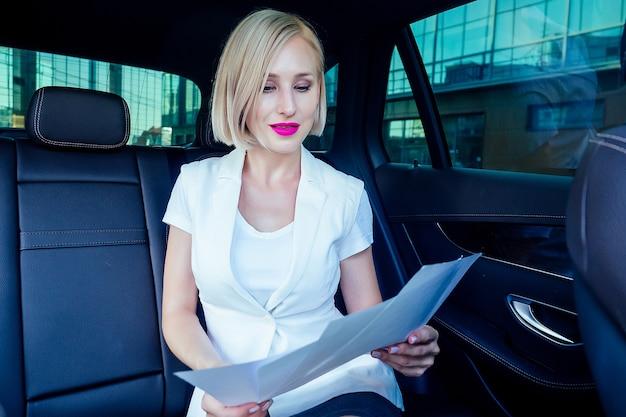 Portret van mooie jonge succesvolle blonde kort kapsel zakenvrouw met make-up felle lippenstift in witte pak jurk zittend op een leren stoel werkt met effecten in auto