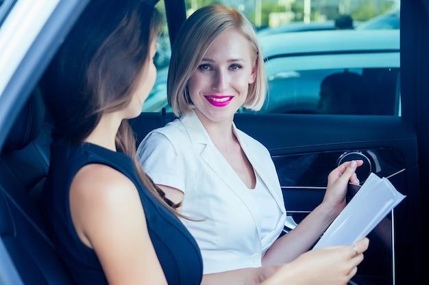 Portret van mooie jonge succesvolle brunette en blonde zakenvrouwen contract handtekening in auto werken met laptop en effecten in pak jurk. goede deal kopen en verkopen concept.