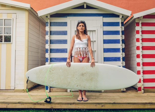 Portret van mooie jonge surfer vrouw met witte top en bikini surfplank houden over een strand gestreepte hutten. zomer vrije tijd concept.