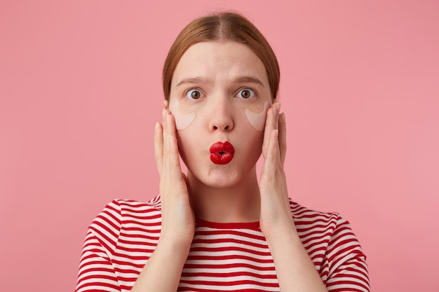 Portret van mooie jonge verbaasde roodharige dame in een rood gestreept t-shirt, met rode lippen en met vlekken onder de ogen, verbaasde blikken en stands.