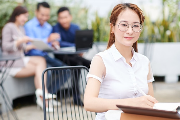 Portret van mooie jonge vietnamese zakenvrouw in glasplaten aan café tafel zitten en schrijven in planner