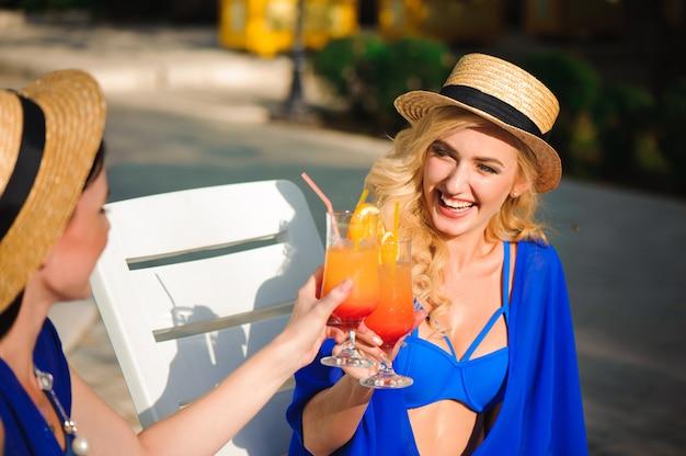 Portret van mooie jonge vrienden die en cocktails in een pool glimlachen drinken.