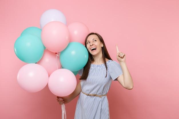 Portret van mooie jonge vrolijke vrouw in blauwe jurk met kleurrijke luchtballonnen wijzende wijsvinger omhoog op kopie ruimte geïsoleerd op heldere trending roze achtergrond. verjaardagsfeestje concept.