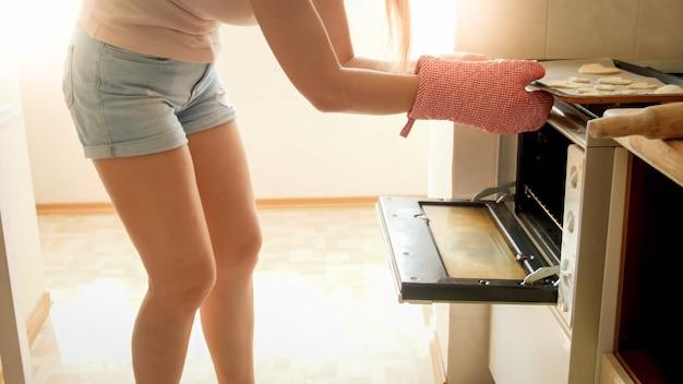 Portret van mooie jonge vrouw die bakpan met koekjes in de hete oven bij keuken zet