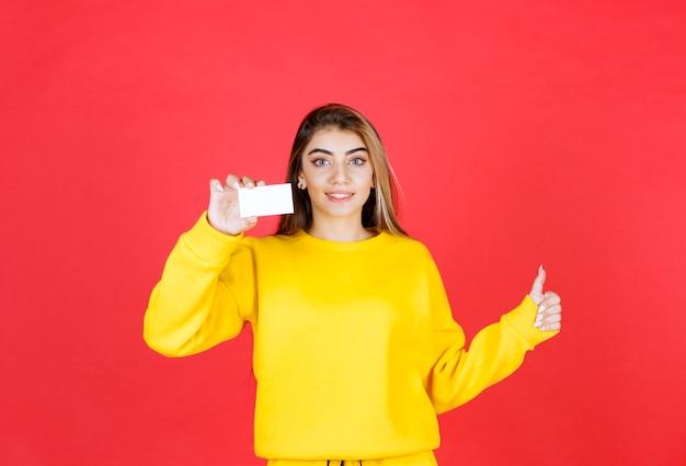 Portret van mooie jonge vrouw die blanco visitekaartje toont