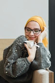 Portret van mooie jonge vrouw die een koffie houdt