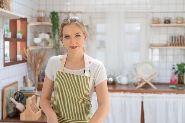 Portret van mooie jonge vrouw die gezond voedsel maakt in de keukenkamer thuis.