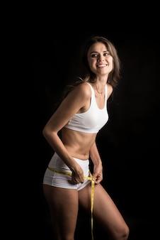 Portret van mooie jonge vrouw die haar cijfergrootte met meetlint meet