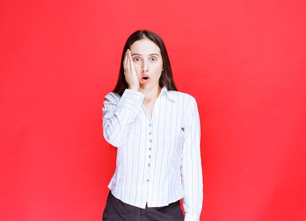 Portret van mooie jonge vrouw die haar hoofd op rode achtergrond houdt.