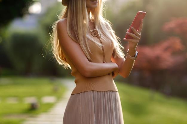Portret van mooie jonge vrouw die haar mobiele telefoon in de straat met behulp van.