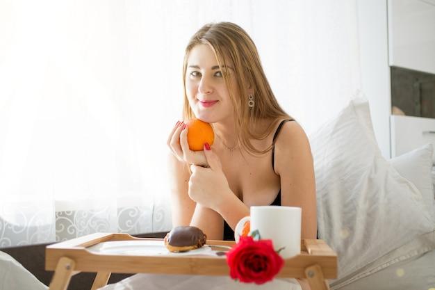 Portret van mooie jonge vrouw die in bed ligt en sinaasappel vasthoudt