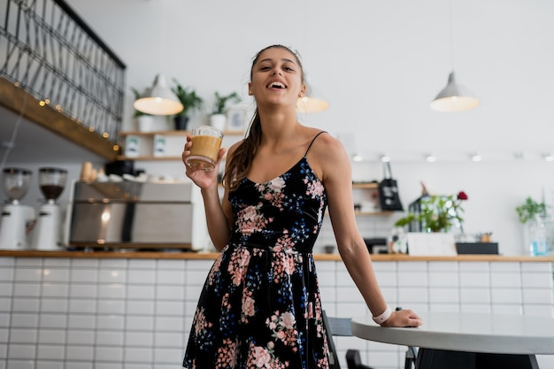Portret van mooie jonge vrouw die in de ochtend koffie gaat drinken