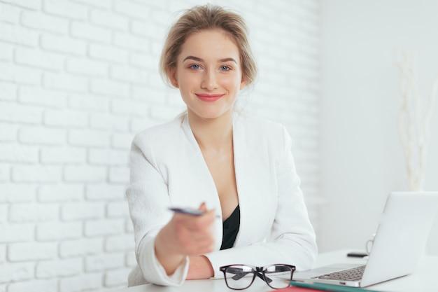 Portret van mooie jonge vrouw die in het bureau werkt.