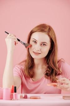 Portret van mooie jonge vrouw die make-up toepast bij het klaarmaken in de ochtend
