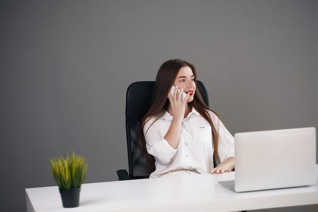 Portret van mooie jonge vrouw die met laptop in haar bureau werkt.