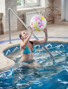 Portret van mooie jonge vrouw die met strandbal speelt bij zwembad