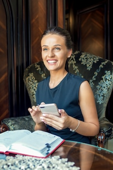 Portret van mooie jonge vrouw die mobiele telefoon thuis met behulp van.