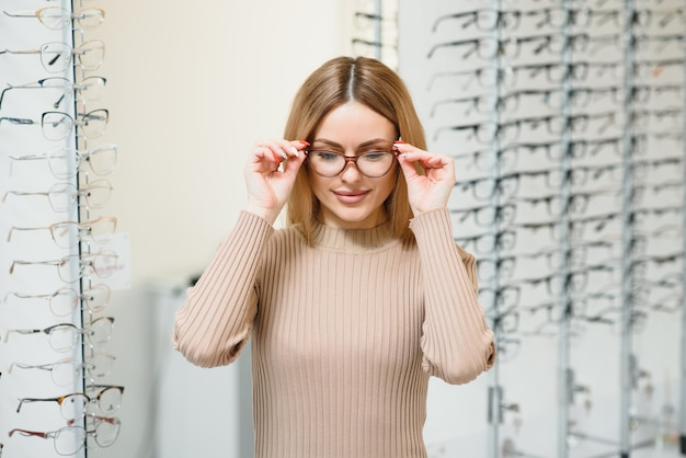Portret van mooie jonge vrouw die nieuwe glazen in opticienopslag probeert