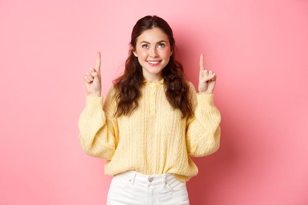 Portret van mooie jonge vrouw die, omhoog wijst en naar hoogste promo-aanbieding glimlacht, reclame toont, promotietekst leest, die zich tegen roze muur bevindt.