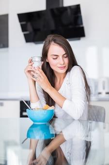 Portret van mooie jonge vrouw die ontbijt in de keuken heeft.