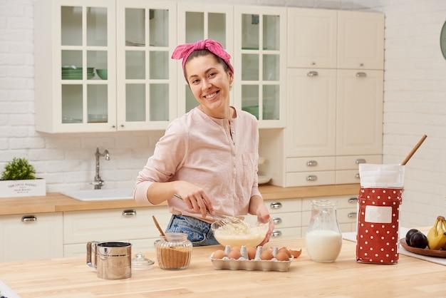 Portret van mooie jonge vrouw die ontbijt in de keuken heeft
