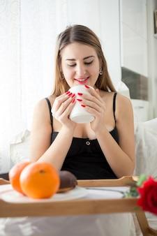 Portret van mooie jonge vrouw die ontbijt op bed heeft en koffie drinkt