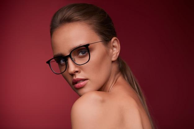 Portret van mooie jonge vrouw die oogglazen draagt. sensueel fotomodel