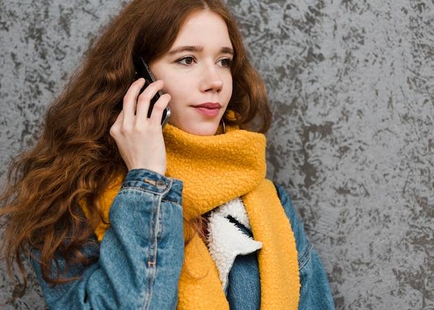 Portret van mooie jonge vrouw die op de telefoon spreekt