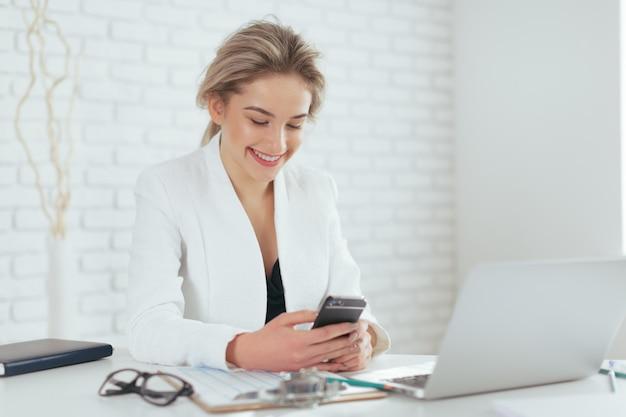 Portret van mooie jonge vrouw die op kantoor werkt.
