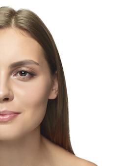 Portret van mooie jonge vrouw die op witte studiomuur wordt geïsoleerd