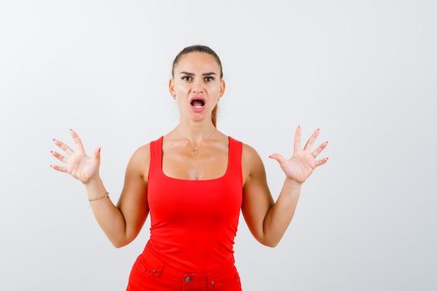 Portret van mooie jonge vrouw die overgave gebaar in rood mouwloos onderhemd tonen en geschokt vooraanzicht kijkt