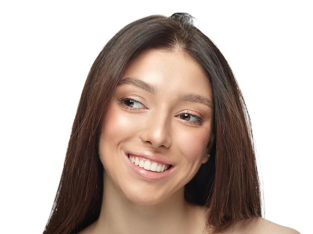 Portret van mooie jonge vrouw geïsoleerd op een witte muur. kaukasisch gezond vrouwelijk model dat naar de zijkant kijkt, glimlacht mooi. concept van de gezondheid en schoonheid van vrouwen, zelfzorg, lichaam, huidverzorging.
