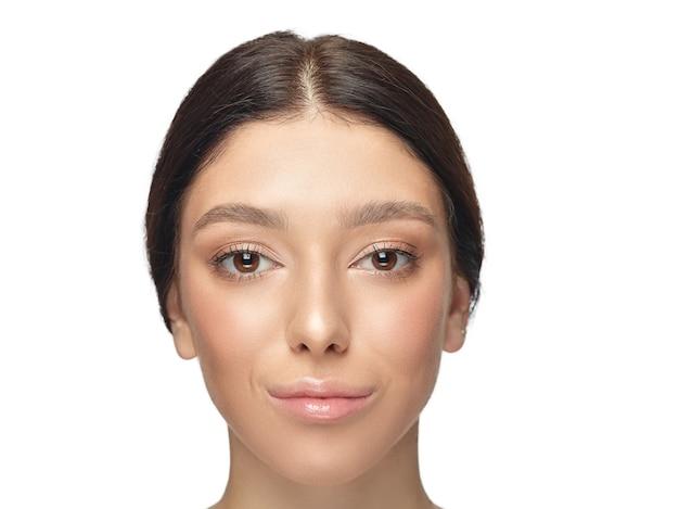 Portret van mooie jonge vrouw geïsoleerd op een witte muur. kaukasisch gezond vrouwelijk model en poseren. concept van de gezondheid en schoonheid van vrouwen, zelfzorg, lichaams- en huidverzorging.