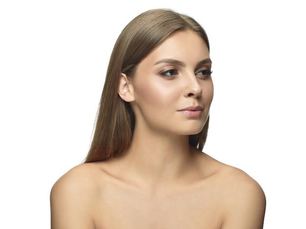Portret van mooie jonge vrouw geïsoleerd op een witte muur. kaukasisch vrouwelijk model kant kijken en poseren. concept van gezondheid en schoonheid van vrouwen, zelfzorg, lichaams- en huidverzorging.