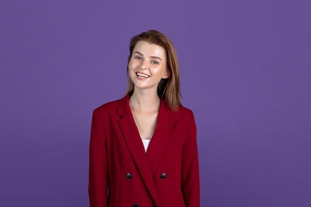 Portret van mooie jonge vrouw geïsoleerd op paarse studio
