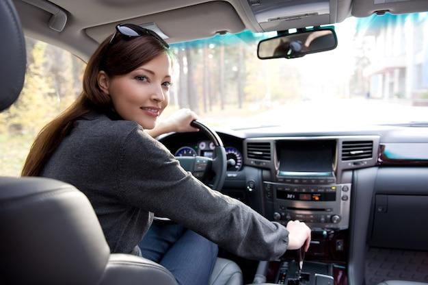 Portret van mooie jonge vrouw in de nieuwe auto