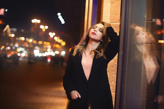 Portret van mooie jonge vrouw in het zwart op een achtergrond van een nachtstad. nachtleven
