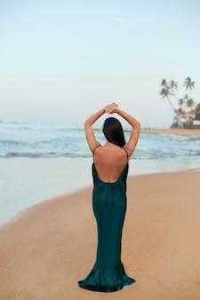 Portret van mooie jonge vrouw in jurk op het strand. achteraanzicht van mooi meisje op tropisch strand. vrijheidsconcept, vakantie, strand, hemelachtergrond.