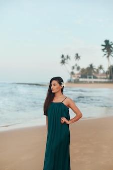 Portret van mooie jonge vrouw in jurk op het strand. mooi meisje op tropisch strand. vrijheidsconcept, vakantie, strand, hemelachtergrond.