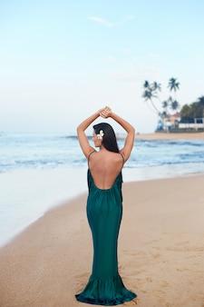Portret van mooie jonge vrouw in lange groene jurk op het strand met een bloem op haar haar