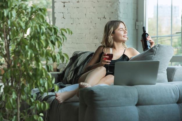 Portret van mooie jonge vrouw in moderne appartement in de ochtend. rusten, kalm, gebalanceerd. jeugd en wellness-concept.