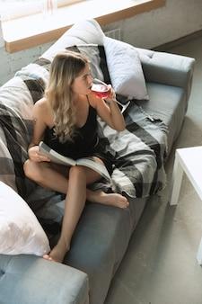 Portret van mooie jonge vrouw in moderne appartement in de ochtend