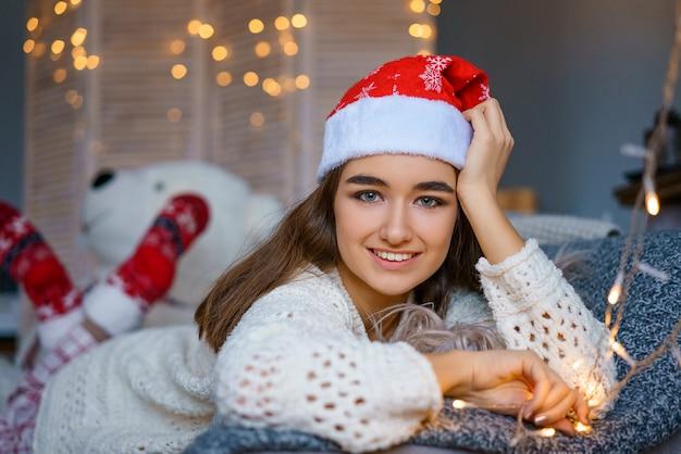 Portret van mooie jonge vrouw in santa claus-hoed op bokehachtergrond